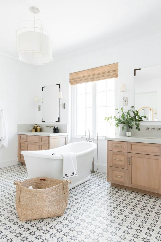a modern rustic bathroom with a lovely patterned tile floor, stained vanities, a basket and shades plus a vintage inspired tub