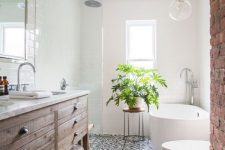 a modern rustic bathroom with white walls and a mosaic tile floor, a rough wooden vanity and white appliances plus a potted plant
