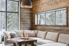 a modern rustic living room fully clad with wood, with a large neutral sectional, a coffee table and a pendant lamp