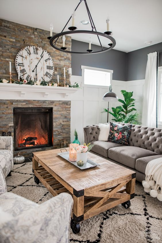 a modern rustic living room with a fireplace clad with faux stone, neutral furniture, a metal chandelier, a wooden coffee table