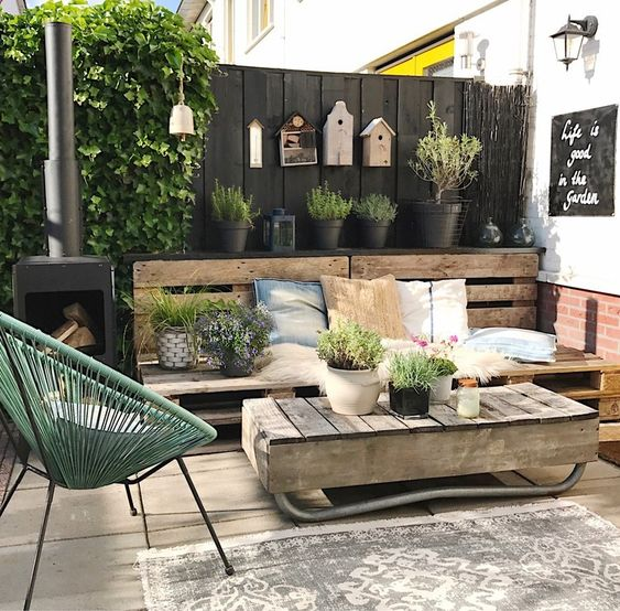 a modern rustic terrace with a pallet bench, pretty textiles, a pallet coffee table, a green chair and a hearth plus potted greenery