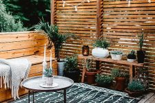 a modern rustic terrace with a wooden deck, built-in benches with a blanket, a bench with potted plants and some lights over the space