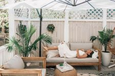 a modern tropical patio with wooden furniture, a woven side table, potted plants, layered rugs and an umbrella over the space