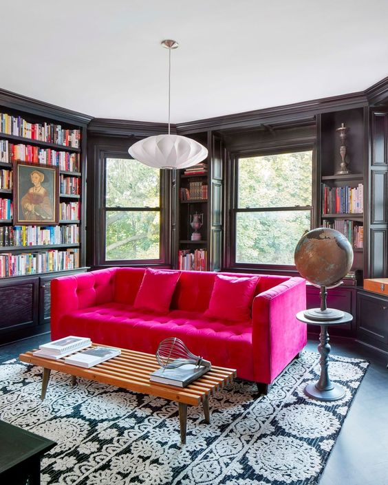 a moody and elegant black home library with lots of bookshelves, a hot pink sofa and a printed rug, a globe and a pendant lamp