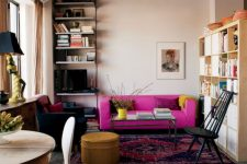a moody apartment with an industrial feel, blush walls and a black ceiling, a hot pink sofa for a bold color statement