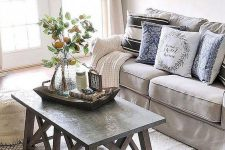 a neutral farmhouse living room with grey furniture, a wood and concrete coffee table, a large clock and printed textiles