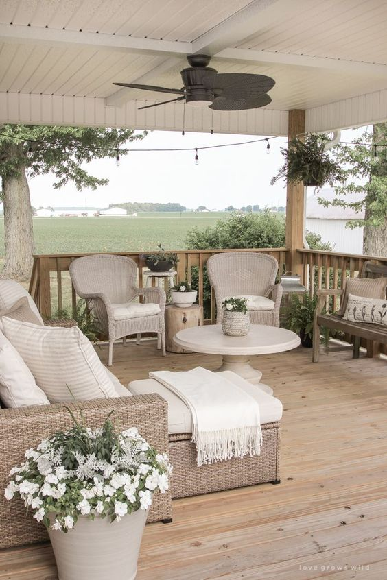 a neutral farmhouse porch with a wooden deck, wicker furniture, potted plants and blooms, a bench and tree stump side tables