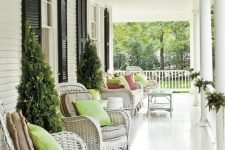 a neutral farmhouse porch with white wicker furniture, neutral and green pillows, some greenery and Christmas trees