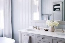 a neutral bathroom design with a planked wall