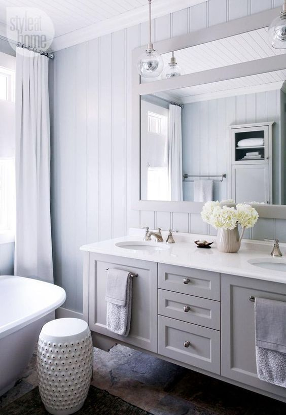 a neutral modern country bathroom with pale blue planked walls, a floating grey vanity, a large mirror, pendant lamps and neutral textiles