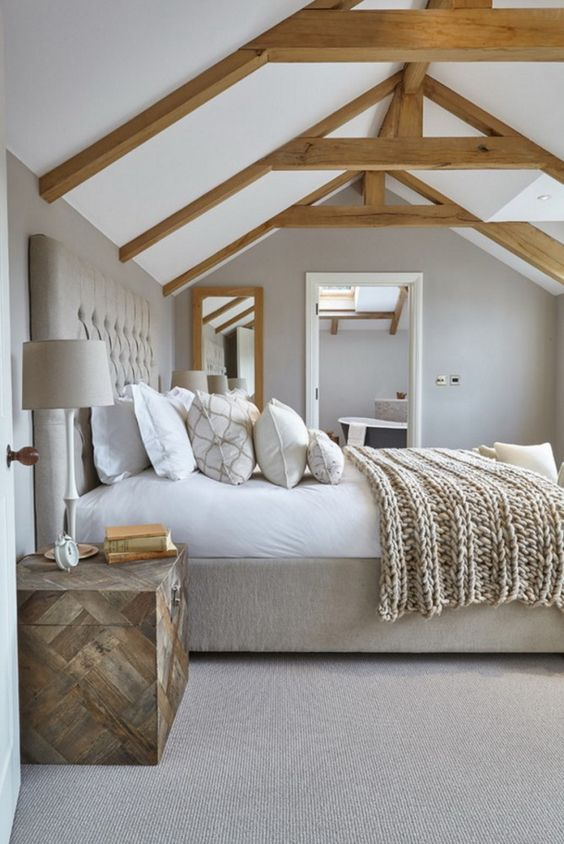 a neutral modern country bedroom done in grey, with wooden beams and an upholstered bed, a wooden chest and neutral bedding