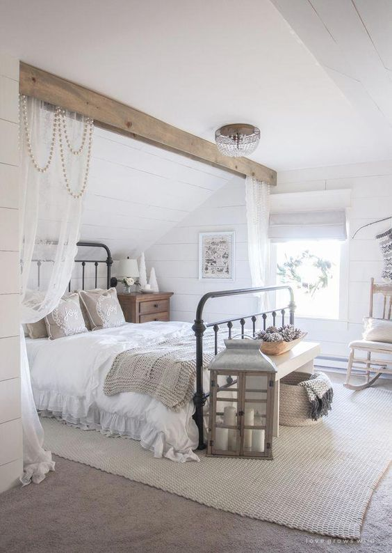 a neutral modern country bedroom with white planked walls, a wooden beam over the metal bed, neutral furniture and a large candle lantern
