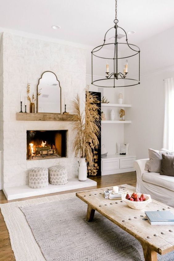 a neutral modern country living room with a fireplace clad with brick, a low coffee table, neutral furniture and layered rugs