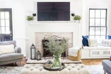 a neutral modern farmhouse living room with a fireplace clad with brick, neutral furniture and built-in daybeds, an upholstered ottoman and a fan