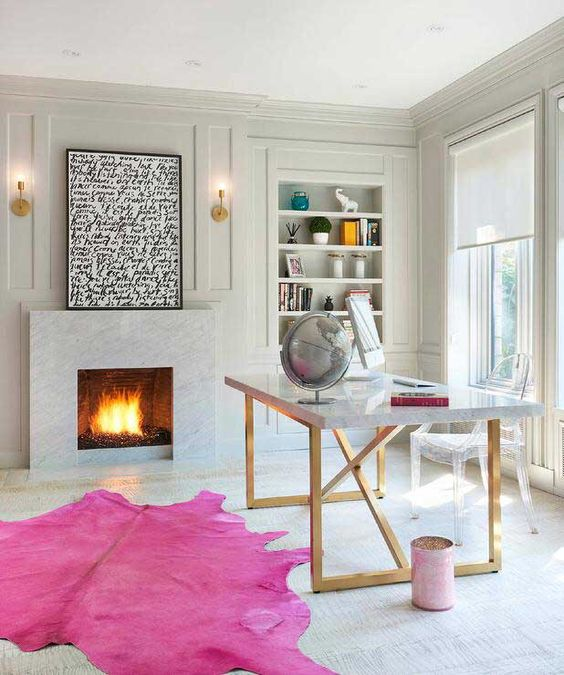 a neutral yet quirky home office with built-in shelves, a fireplace with an artwork, a chic desk and a ghost chair and a hot pink rug