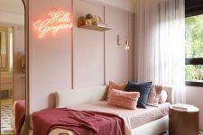 a pale pink paneled accent wall, a creamy daybed with comfy pillows, a neon sign, a large mirror and a round side table