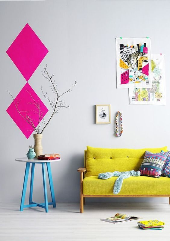 a pretty and bright interior with a lemon yellow loveseat, a table with blue legs, a colorful gallery wall and hot pink geometric decor