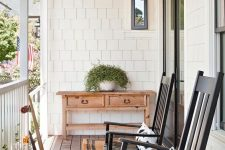 a pretty and simple farmhouse porch with a vintage console table, black rockers and printed pillows, potted greenery and some lanterns is welcoming