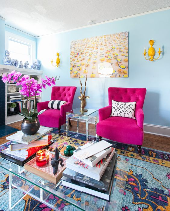 a quirky living room with light blue walls, hot pink chairs, yellow sconces, a glass table with books and hot pink orchids