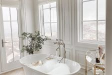 a refined and chic fancy bathroom with white paneled walls, windows, a luxurious bathtub, a crystal chandelier and a potted plant