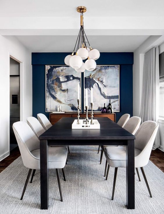 a refined and elegant dining room with a navy accent wlal, beautiful artworks, a long black table, creamy chairs and a cluster of pendant lamps