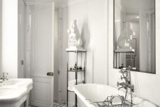 a refined and luxurious bathroom with white walls, a mosaic tile floor, a white vintage tub and an oversized mirror and a gold chandelier