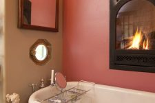 a refined bathroom with a pink accent wall and a built-in fireplace, a black vintage bathtub, a sculpture, a mirror in an ornated frame, a sconce and a mosaic tile floor