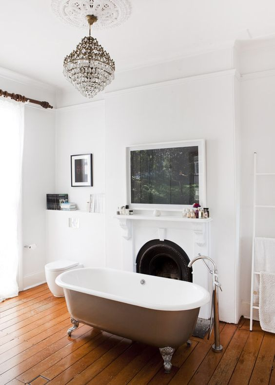 a refined bathroom with a rich-stained wooden floor, a non-working fireplace, lovely artworks, a crystal chandelier and a lovely bathtub