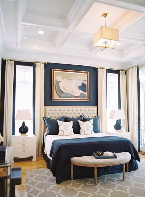 a refined bedroom with a navy accent wall, a creamy upholstered bed, navy and white bedding, creamy curtains and white nightstands