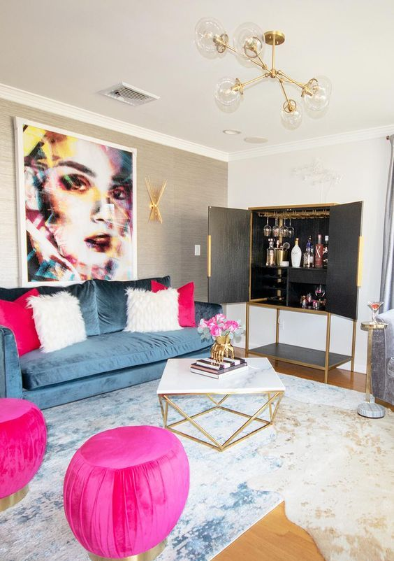 a refined living room with a blue sofa, hot pink poufs and pillows, an elegant geometric table and a home bar