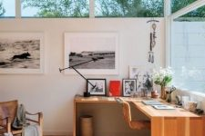 a refined modern country home office with a corner wooden desk, leather chairs, a small gallery wall and some blooms
