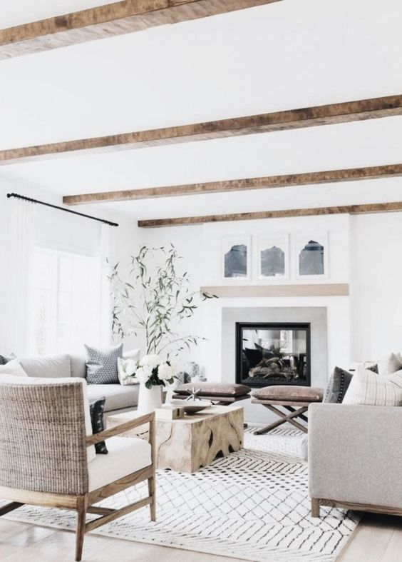a refined modern country living room with a large fireplace, wooden beams, comfy furniture, a low wooden table and leather stools