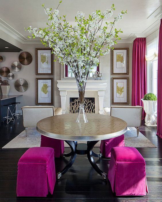 a refined space done in neutrals, with a fireplace clad with beautiful screen, hot pink curtains and a round mirror with hot pink poufs
