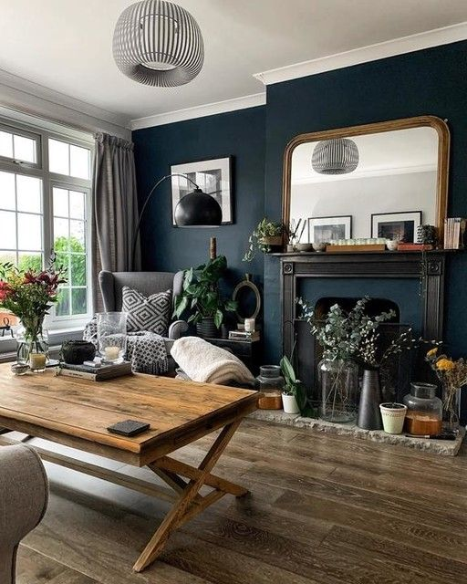 a refined vintage living room with a navy accent wall, a fireplace, a mirror in a gilded frame, a trestle table, grey chairs and cool lamps