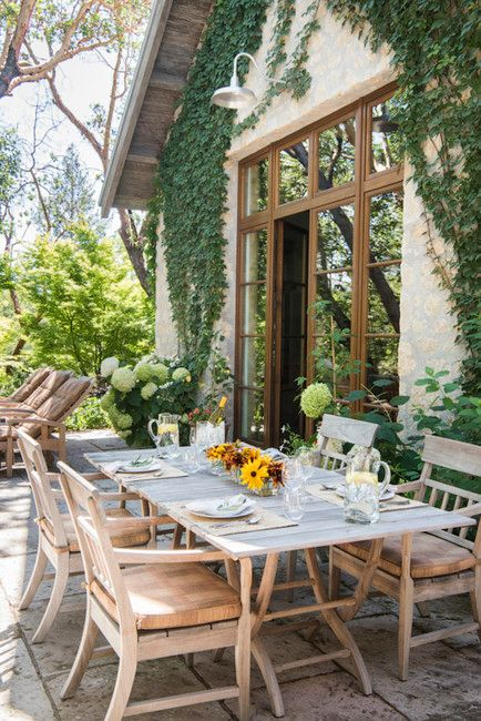 a simple and cozy modern country terrace with a whitewashed wooden dining set and some loungers, some potted plants