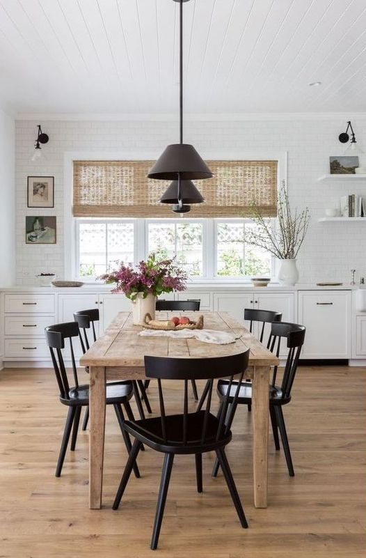 a simple modern farmhouse dining space with a stained wooden table, vintage black chairs, modern black pendant lamps is cool