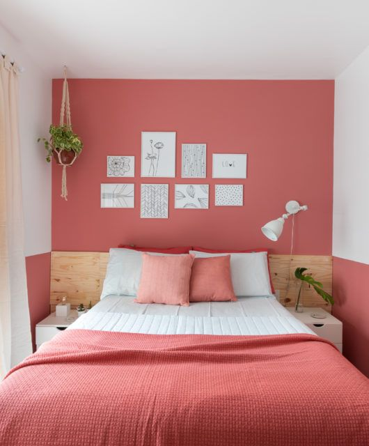 a small and bold bedroom with a salmon pink accent wall plus matching bedding, some potted plants and a cool white sconce is pure chic