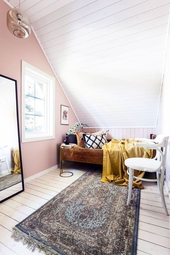 a small attic bedroom with a pink accent wall, a planked floor and ceiling, a wooden bed with some catchy bedding