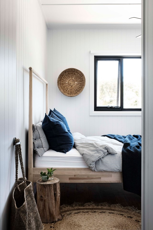 a small bedroom with white planked walls, a wooden bed, a jute rug, a tree stump side table, a decorative basket and navy and striped bedding