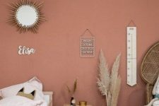 a small boho kid's bedroom with a pink accent wall, simple wooden furniture and a peacock chair, a sunburst mirror and pampas grass