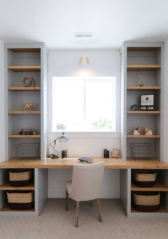a small modern country home office in dove grey, with built-in shelvin units and a desk, an upholstered chair and a sconce