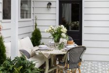 a small modern farmhouse terrace with mosaic tiles, vintage and modern wooden and rattan furniture, potted plants and blooms and lights over the space