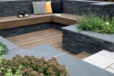 a small sunken outdoor space with a wooden deck, a built-in bench and growing plants and blooms is a lovely space to be