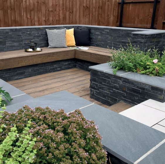 a small sunken outdoor space with a wooden deck, a built in bench and growing plants and blooms is a lovely space to be