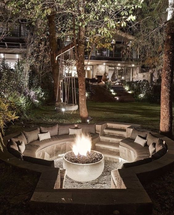 a small sunken patio with a fire pit and built-in round benches with pillows is a lovely space to relax in the evening