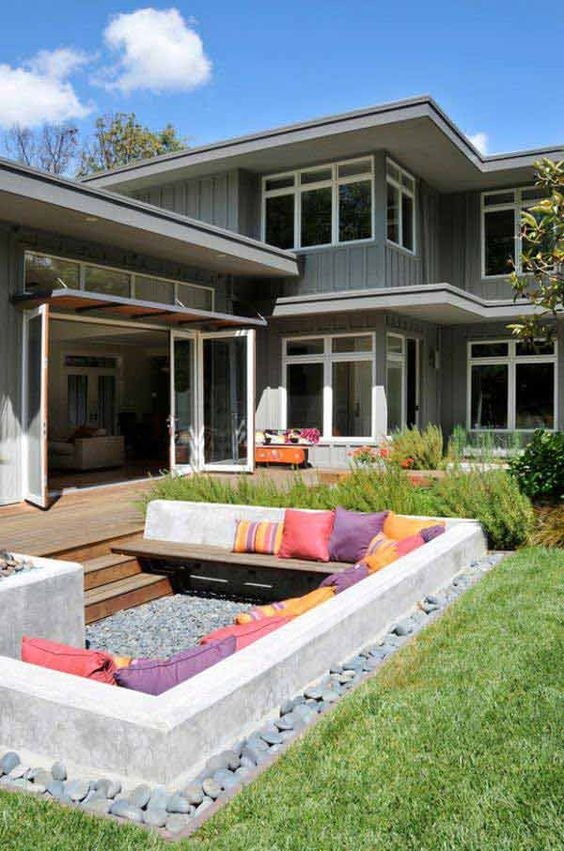 a small sunken patio with gravel on the ground and a large built-in bench accessorized with colorful pillows is a fun and pretty space