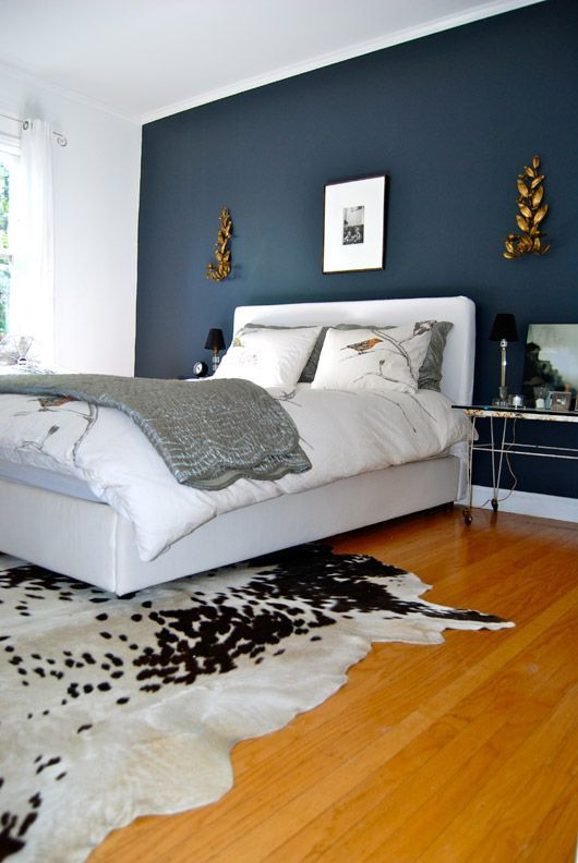 a sophisticated bedroom with a navy accent wall, a white upholstered bed, a cowhide rug, hairpin leg nightstands and some art