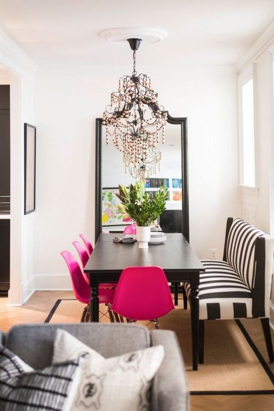 a sophisticated dining room with a black table, a striped bench, hot pink chairs, a chic black chandelier and a floor mirror