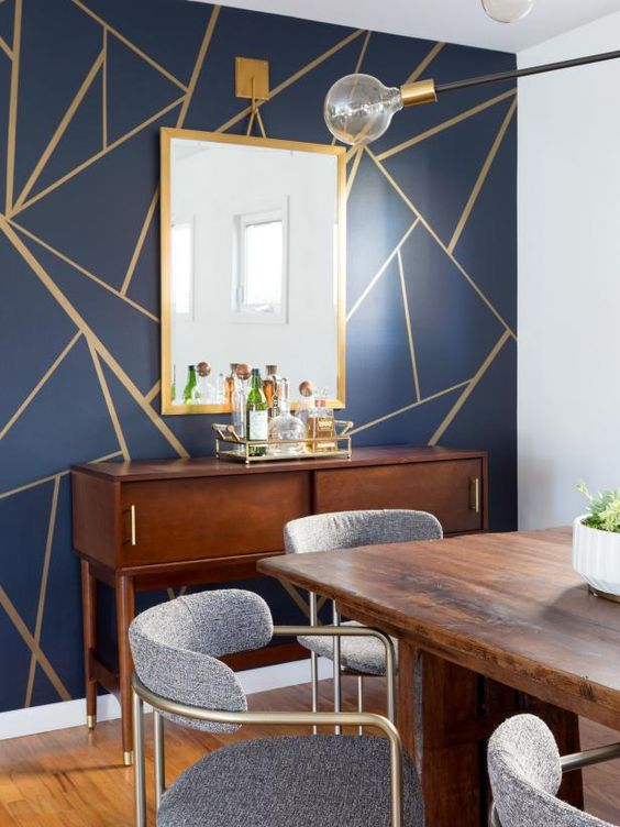 a sophisticated dining room with a navy geometric accent wall, stained furniture, grey chairs and a chic sunburst chandelier and a vintage console