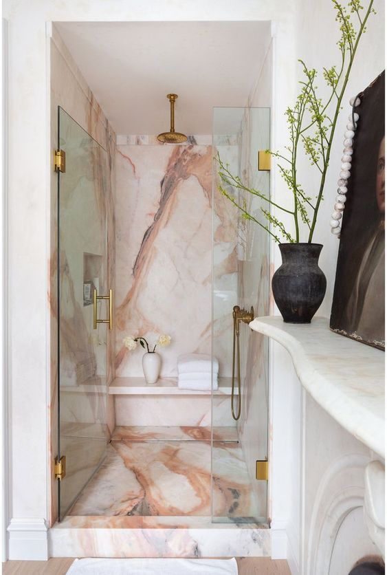 a sophisticated fancy bathroom with a gorgeous pink marble shower space, gold and brass touches and a fireplace right here